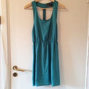 Turquoise dress, zipper in the back (not possible to zip-up). Never used. 100% polyester.
