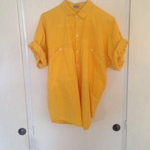 Gul skjorta med fickor, vita knappar.