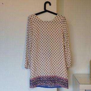 Långärmad mönstrad klänning i beige/ljusrosa aktig färg. Aldrig använd med lappar kvar!