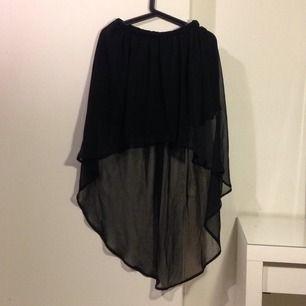 Svart kjol som är kortare fram än bak. Transparent tyg i