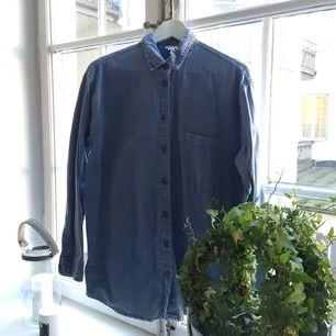 Oversize jeansskjorta från Monki. Sliten blå färg med bruna knappar. Fint skick.