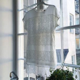 Fin klänning från Jeane Blush i offwhite. Vackra spetsdetaljer. Sprund bak i ryggen med dekorativ knapp. Använd endast en gång.