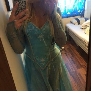 Elsa-klänning från Coolstuff.se i stl S. Använd en gång. Med klänningen medföljer en tiara och en pälskrage i fuskpäls.  Denna vill jag mötas upp med då den levereras i originalförpackningen 🎀