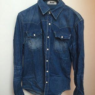 Jeansskjorta frän Acne i strl 46. Vänster bröstfickas knapp är dålig men märks inte