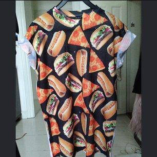 Skön t-shirt med pizza/hambörjare/korv-tryck köpt på Primark av 100% polyester. Inte jättetight men det är inte oversize. Ärmarna är uppsydda så att de är upprullade. Ger gärna mer info det är bara att skriva!