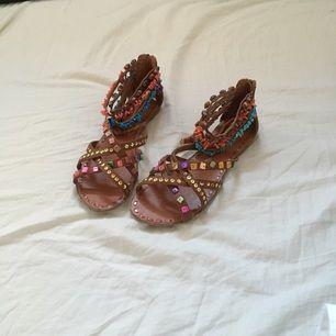 Sandaletter från Scorett, nypris 500 kr. Saknar pärlor på ena bandet på vänstra sandalen (bild 3). Man skulle eventuellt kunna ta bort resten av pärlorna också så att det inte ser trasigt ut. Använda 1-2 gånger!