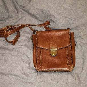 Väska i brunt läder. Ficka med dragkedja på baksidan samt en ficka på framsidan.