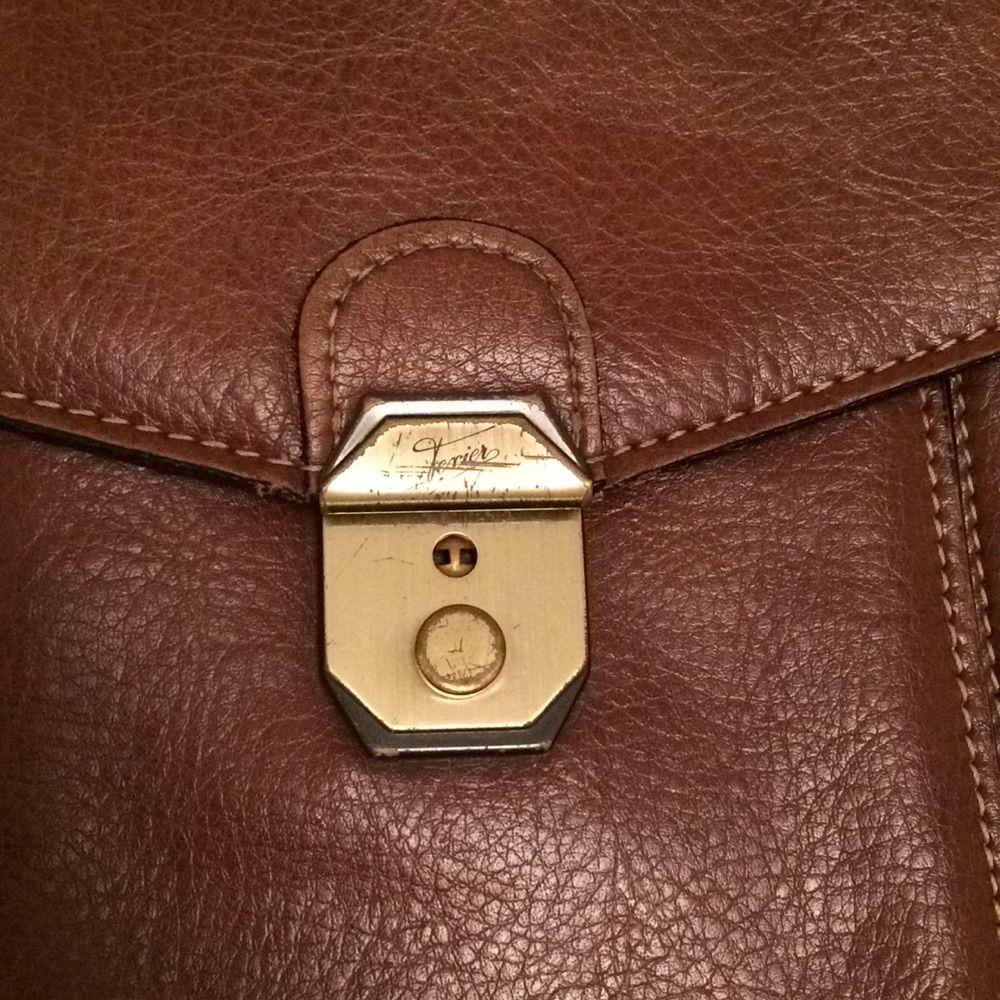 Väska i brunt läder. Ficka med dragkedja på baksidan samt en ficka på framsidan.. Väskor.