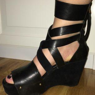 Kilklacksskor från acne i svart läder och mocka. Remmar som går över foten och en dragkedja bak. Jättesköna att gå i!
