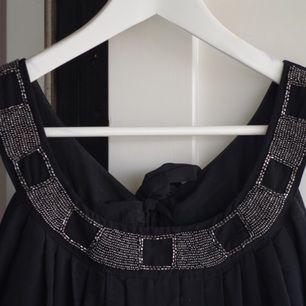 En klänning köpt från HM för många år sedan. Silvriga pärlor framtill och band i ryggen som knyts till en rosett eller vad man nu tycker är snyggt. Den är i mycket bra skick.