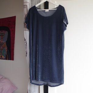 Blå oversized tunika i sametsliknande tyg. Den skimrar i silver, har silvriga knappar hela vägen baktill & köpt på vila.