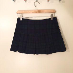 Plisserad skotskrutig kjol köpt i Korea. Tyget är som flanell och är mörkgrönt/marint. Låg midja och väldigt kort.