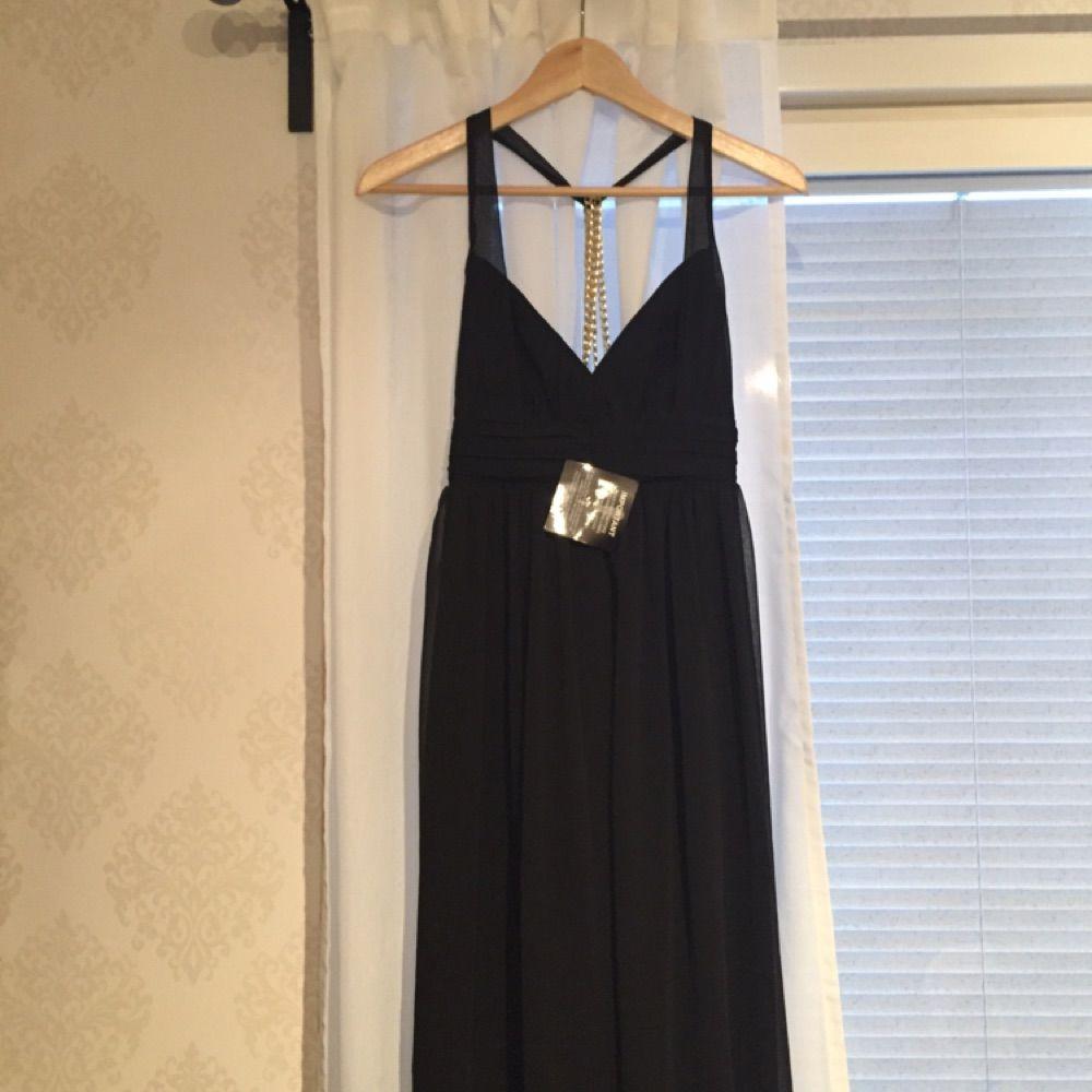 d293a54c8246 Svart långklänning från Nelly Trend. Halterneckmodell med guldkedjor i  ryggen.