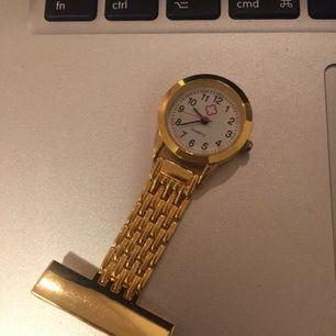 Så kallad sjuksköterske-klocka. Klocka att ha inom vården, brosch med nål. Guldfärgad.