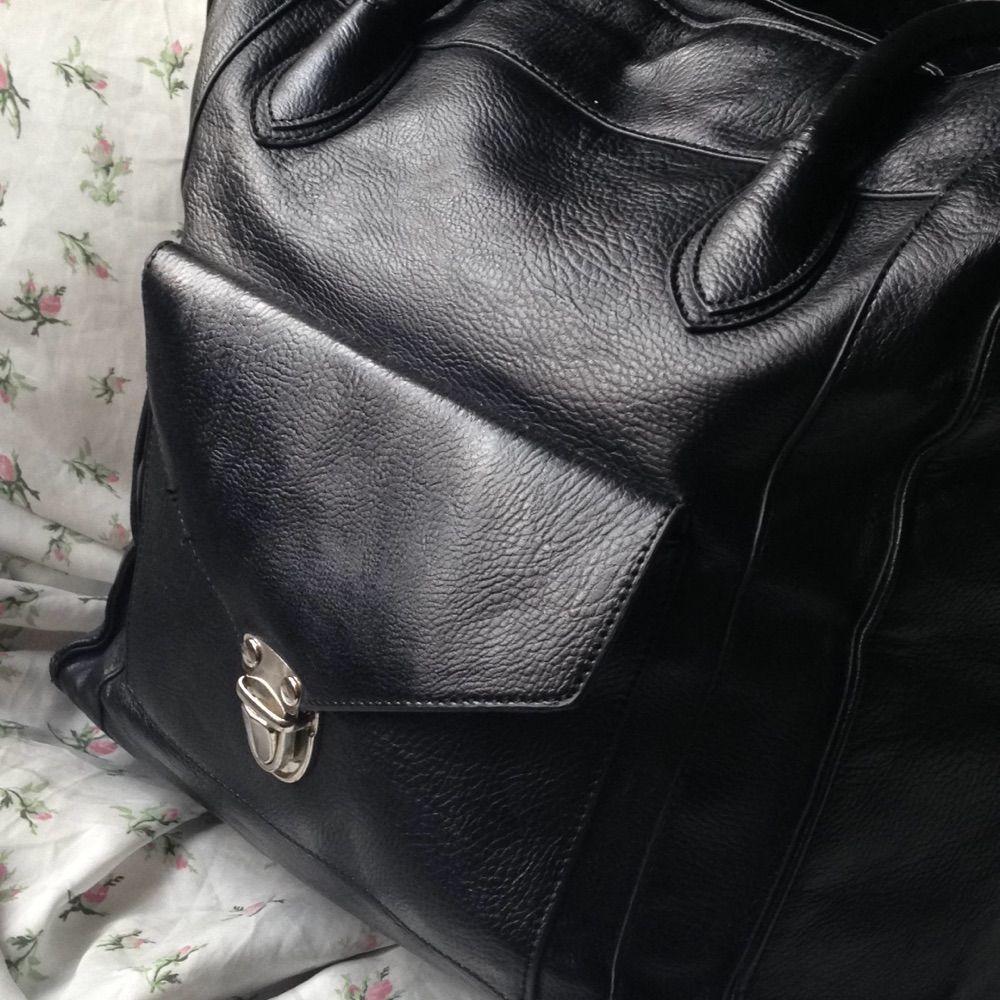 Svart handväska i faux läder.  Snygga detaljer. Silverfärgat spänne på facket på framsidan. Mycket rymlig. Innerfack med dragkedja. Tillhörande axelrem som går att haka fast (se bild 2). Dragkedja till stora facket (se bild 2).  Höjd: 33 cm Bredd: 29 cm Djup: 15,5 cm. Väskor.
