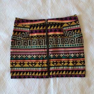 Kjol i stretch med dragkedja och två fickor. Aztekmönster med skarpa färger. Jättefint skick.