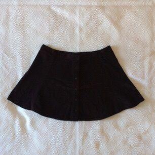 Svart kjol i manchestertyg med sammetskänsla. Ganska vid kjol och stor i storleken. Skulle säga att den passar en större L eller XL. Knäppning framtill med svarta knappar. Jättefint skick.