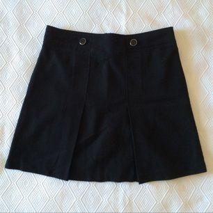 Svart veckad kjol med två silverknappar. Väldigt fint material och superfint skick.