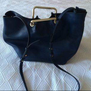 Blå väska med axelrem och rektangulära handtag i metall. Innerfack med dragkedja. Sprillans ny och oanvänd.