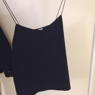 Svart linne med tunna axelband, köpt på bik bok. Den är använd endast ett par gånger.