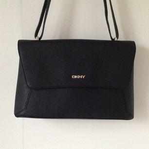Väska från DKNY, perfekt storlek! Justerbar rem och mäter ca 20x30cm. Små förslitningsskador främst på metalldelarna men all in all i väldigt bra skick.  Frakt ok men då står du för det:))
