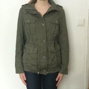 Militärgrön vår/höstjacka från H&M i storlek 42. Se hur den sitter, jag har vanligtvis storlek 36-38. Dragsko i midjan och många fickor!