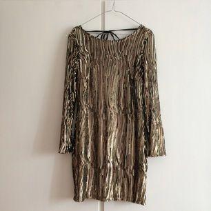 Guldpaljettklänninh i stretchigt material, aldrig använd. Lite urringad i ryggen + knytning i ryggen!