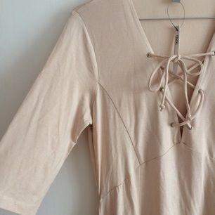 Trikåklänning i gammelrosa/ljusrosa/rosabeige ton med snörning över bröstet, aldrig använd med asos-lappen kvar.