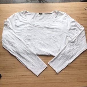 Långärmad tröja i stretchigt material. Avklippt i ärmar och längst ner vilket ger fint rullade kanter
