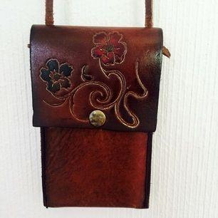 Mobilväska, äkta läder med fina detaljer!  Använt till IPhone 4, men funkar till mobiler i samma storlek, till mynt eller annat smått!  Längre band att ha runt halsen!