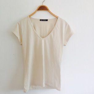 Filippa K, T-shirt. Beige. Storlek L/XL. V-ringad. Använd fåtal gånger. Fint skick!