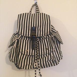 Svart/Vit Randig Ryggsäck. Använd väl men fortfarande i bra skick. Dock har magneten åkt av (foto 3) så det går inte att stänga en av fickorna helt. Den mycket med utrymme och är väldigt enkel att bära med sig.