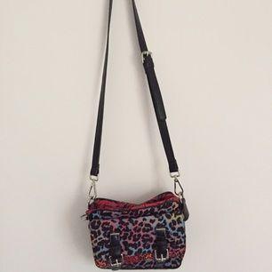 En liten väska med ett färgglatt leoprint från Zara. Väskan har flera olika fack