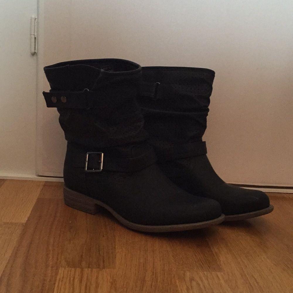 72734599e54 Svart sko i skinnimitation med brun sula och cirka 19 cm högt skaft.