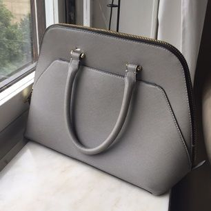 Zara Woman grey handbag with gold zipper. Absolutely love this bag, but it broke at the handel and I cannot fix it myself. Perfect for someone who is handy or has the means to get it fixed. The shoulder strap that came with the bag also broke off. These defects are why the price is low for this item, but if you can restore it, the bag is lovely.  Can pick-up in Stockholm or can send as a package with added delivery charge