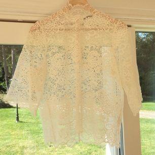 Krämvit tröja i spets. Använd vid ett tillfälle och köpt för 1100:- på cenino donna