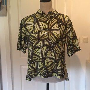 En grön-mönstrad t-shirt/skjorta från Monki. Trots storleken så passar den även en S-M tackvare att modellen är oversize. Knappt använd, så i nyskick!