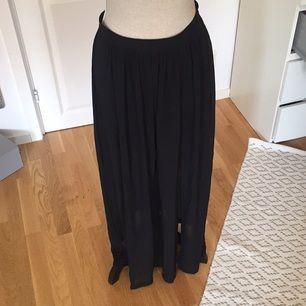 Svart långkjol från H&M med transparent tyg och slits på ena sidan. Har även en innekjol. Använd, men i fint skick!