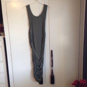 Ursnygg klänning! Prislapp kvar, endast provad.  Klänningen är khaki färgad. På mig som är ca 170 cm lång går den över knäna, vilket är en mycket smickrande och elegant längd. Går dock att dra upp den för att få den kortare, men också att dra ner för att få den som en långklänning.