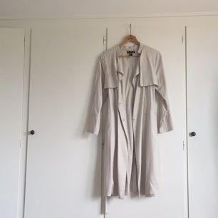 Fin trenchcoat i färgen naturvit/beige/grå från H&M. Sitter jättefint på och har axelvaddar. Sparsamt använd, men ändå en aning nopprig (se sista bild) men är inget som syns.