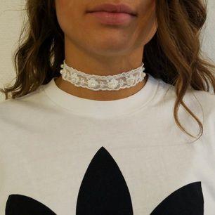Handgjort chokerhalsband i spets med små pärlor. Ställbar storlek, frakt inräknat i priset!