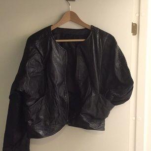 Svart läderjacka av märket Hollies. Lite Grease-känsla med virkade detaljer på ärmarna. Liten vit fläck på magen som går att täcka bort eller ha som den är. Ball fit, men tyvärr lite för stor!