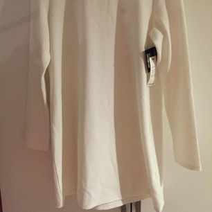 Vit kortare klänning från Nelly. Aldrig använd med lappen kvar! Köparen står för frakten.