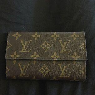 Fake Louis Vuitton plånbok, brun. Lite sönder i högra hörnet där man kan stoppa in foton (sista bilden).