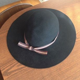 Svart hatt i ull prydd med ett snyggt band. Innermått 55 cm. Brettet mäter 36 cm på bredden och 39 cm på längden. Enda skavanken är att bandet släppt lite baktill, men det fixas lätt med lite lim! Porto 98 kr tillkommer (Shenker), alternativt upphämtning i Gävle.