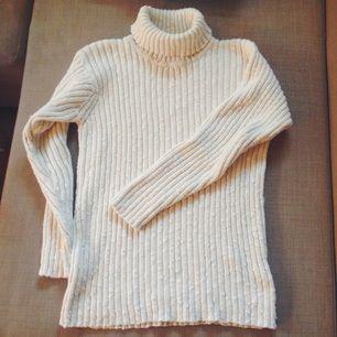 Grovstickad polotröja i en fin benvit färg, från Adelsten. Normal i storlek. Knappt använd och väldigt bra kvalité 🌷