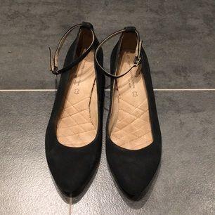 Ballerinas i svart mocka/läder med liten kilklack i träimitation och sjukt skön, stoppad sula.  Säljer pga att jag har knölhälar som inte klarar fästet vid bandet. :-( Skorna är använda på undersidan, men ser i princip oanvända ut på ovansidan.  Storlek UK6 = 39. Köpta på Next, London Köparen står för frakten (billigast möjliga enligt postens ordinarie porto)
