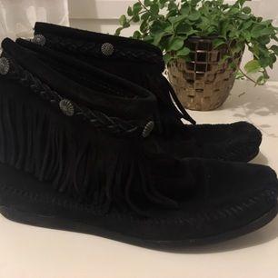 Säljer mina svarta Minnetonka skor. Storlek 7 (skulle säga att de är som 38). Använda men i bra skick. Defekt på insida höger sko där en nit saknas, se bild. Syns inte tydligt när man har dem på sig men därav det låga priset.   Säljs för 400kr, ord pris ca 1000kr.  Kan skickas - då står köparen för frakt. Eller mötas upp runt Kungsbacka/Göteborg. Betalning via Swish.