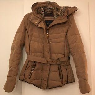 Varm vinterjacka från Zara i beige med guldiga & bruna detaljer. Luvan vadderad med fakepäls.