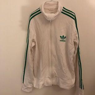 Grön & vit adidas tröja utan fickor. Fint skick, fick den av min bror för hundra år sen men aldrig använt den.